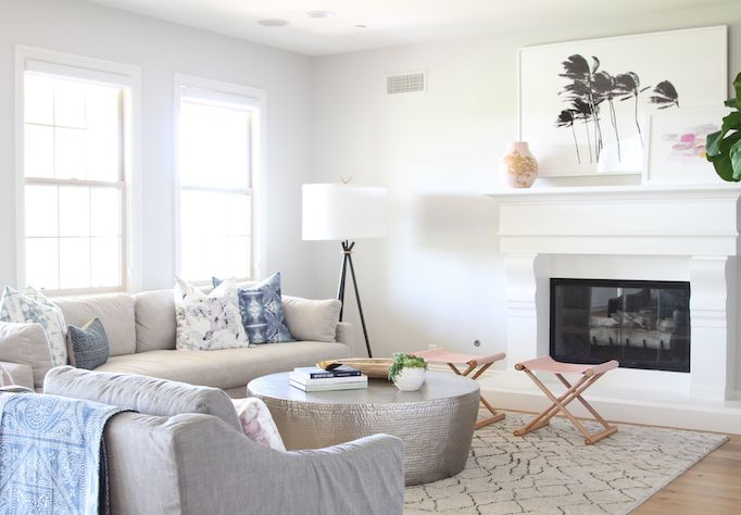 Neutral living room with round coffee table, and soft pink touches.