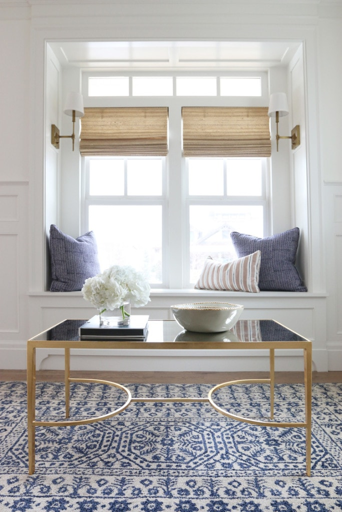 Gold table with glass top. White flowers on top and blue pillows by the window.