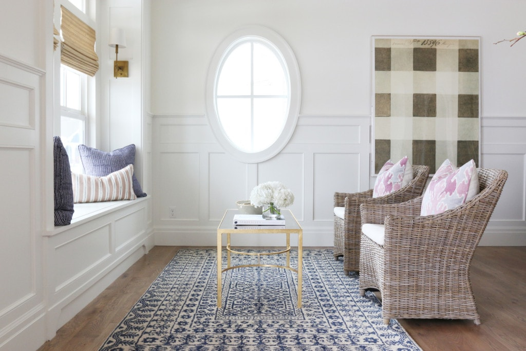 Studio room with oval window, a blue rug, wicker chairs and pillows on the window sill.