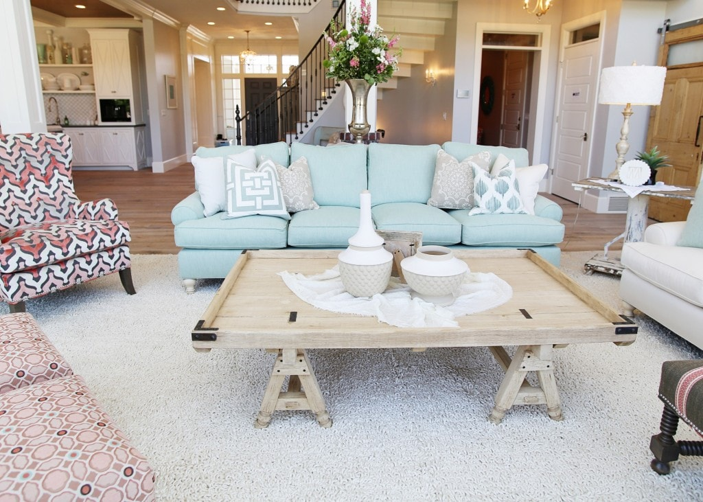 Living room with light blue couch and wooden table.