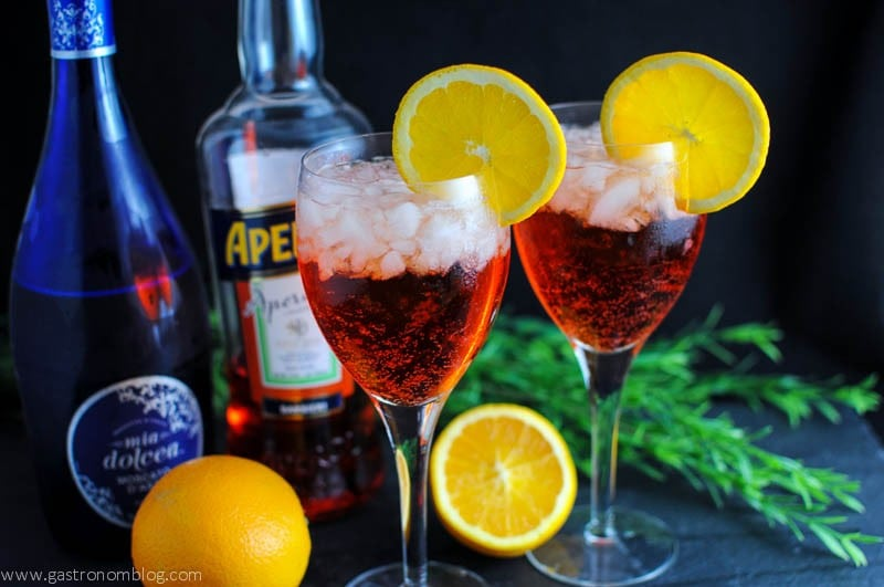 Aperol Spritz in wine glasses with ice cubes and orange slices on the rim.