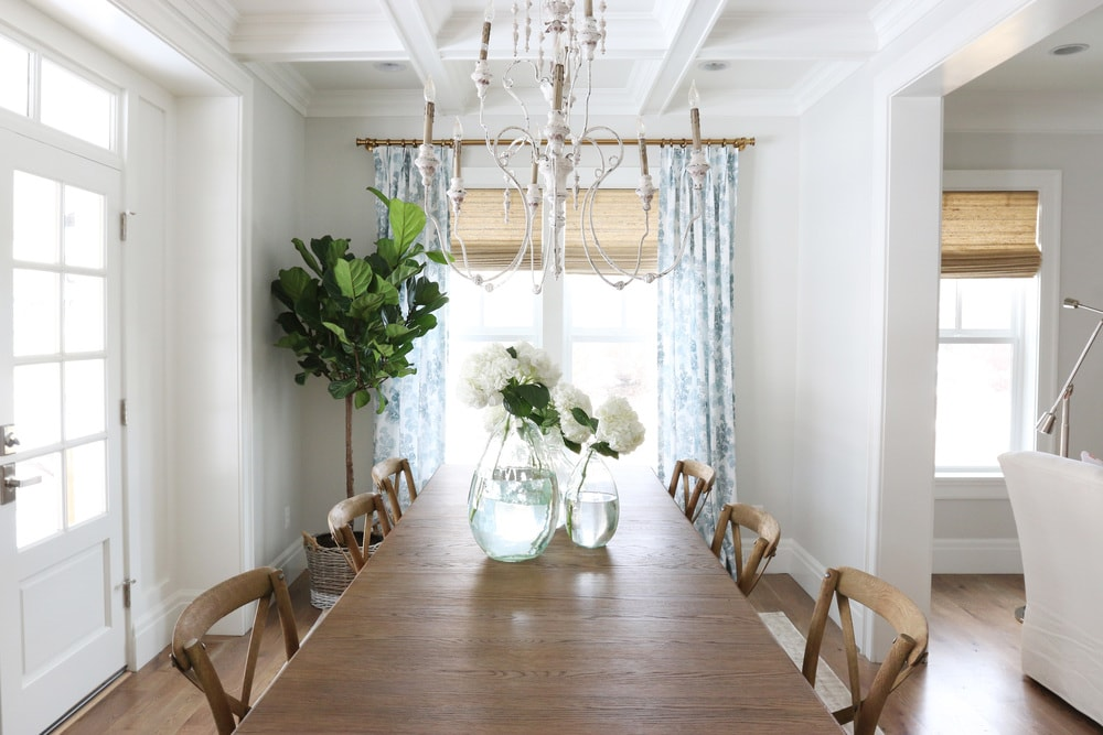 Dining room with a long wooden table and vases with white flowers on the table. A fig leaf tree is in the corner of the room.