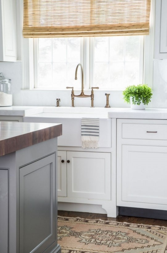 Kitchen with White Cabinets, Gray Island, Blush Pink Runner Rug, Bamboo Roman Shades and Farmhouse Sink