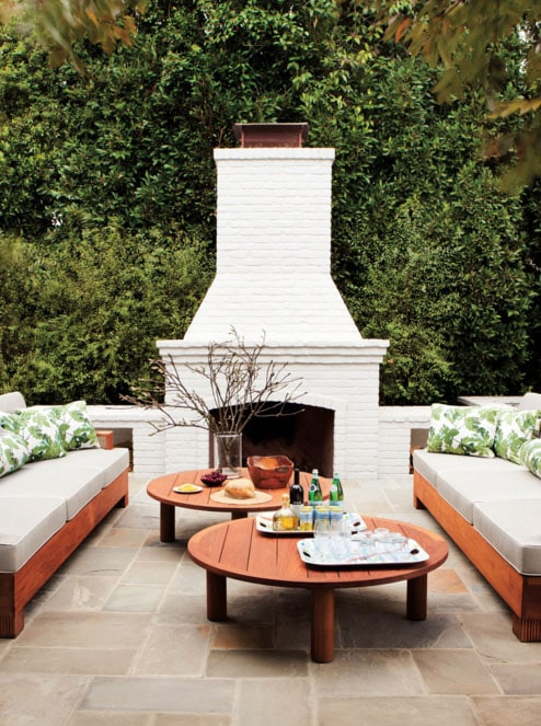 An outdoor space with an outdoor fireplace and fig leaf pillows on the the chairs.