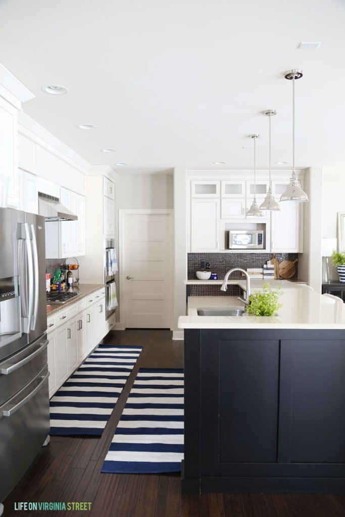 White Kitchen with Black Island and Navy striped runner rugs - Life On Virginia Street