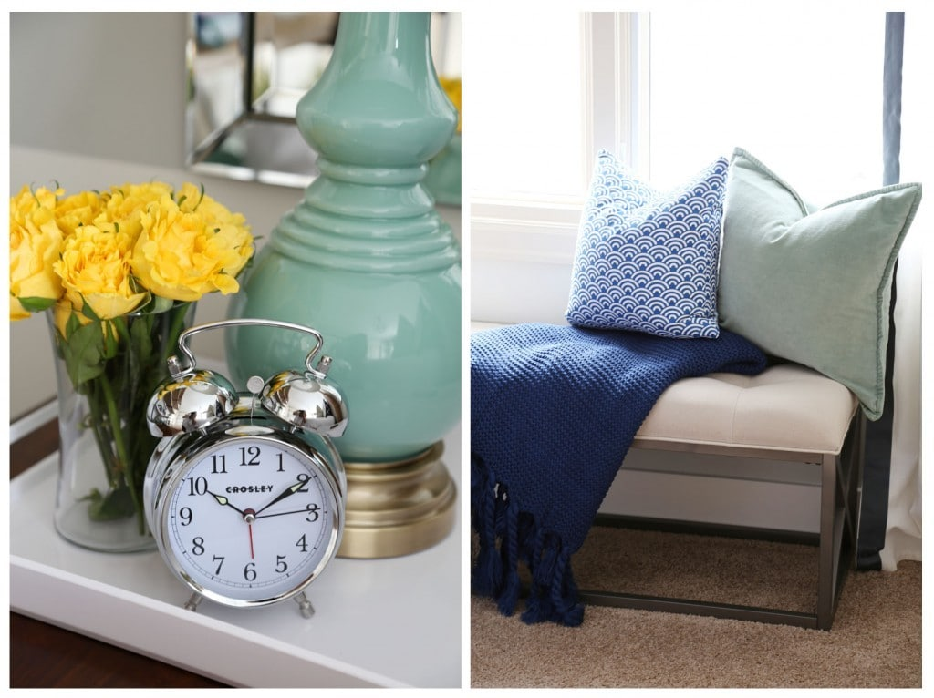 Am alarm clock on the nightstand, yellow flowers and a light green lamp. There is a settee by the window with a blue blanket and pillows.