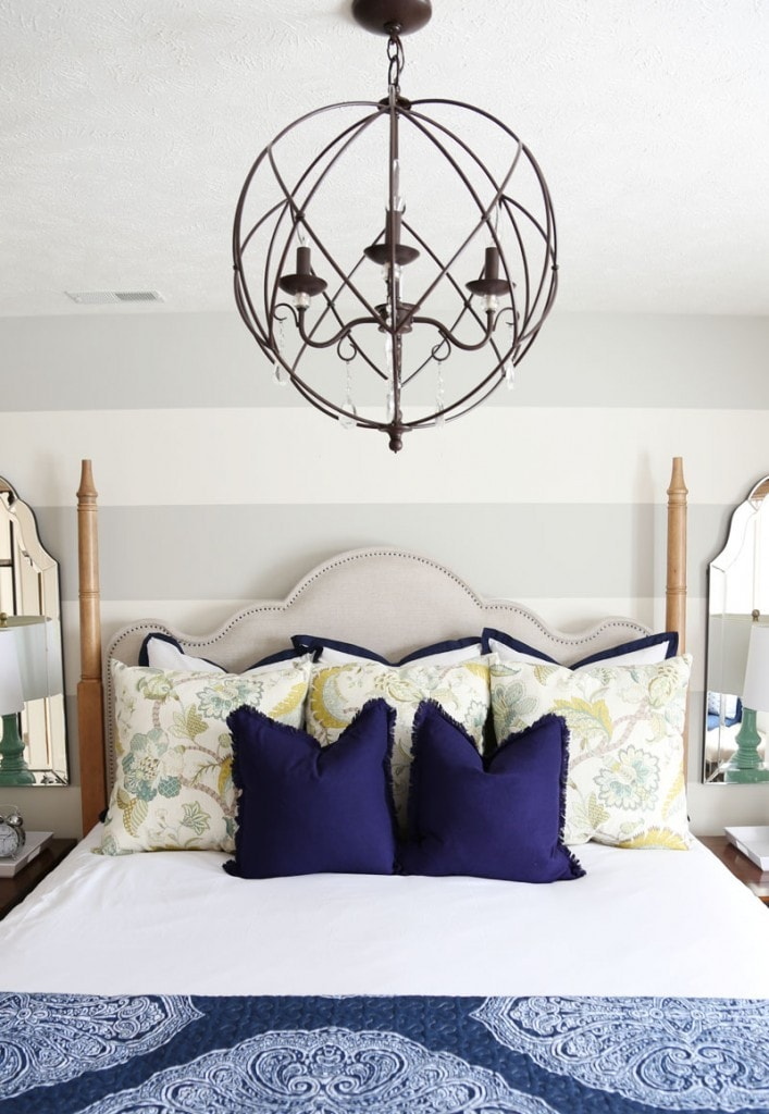 A wrought iron large chandelier over top of the bed.