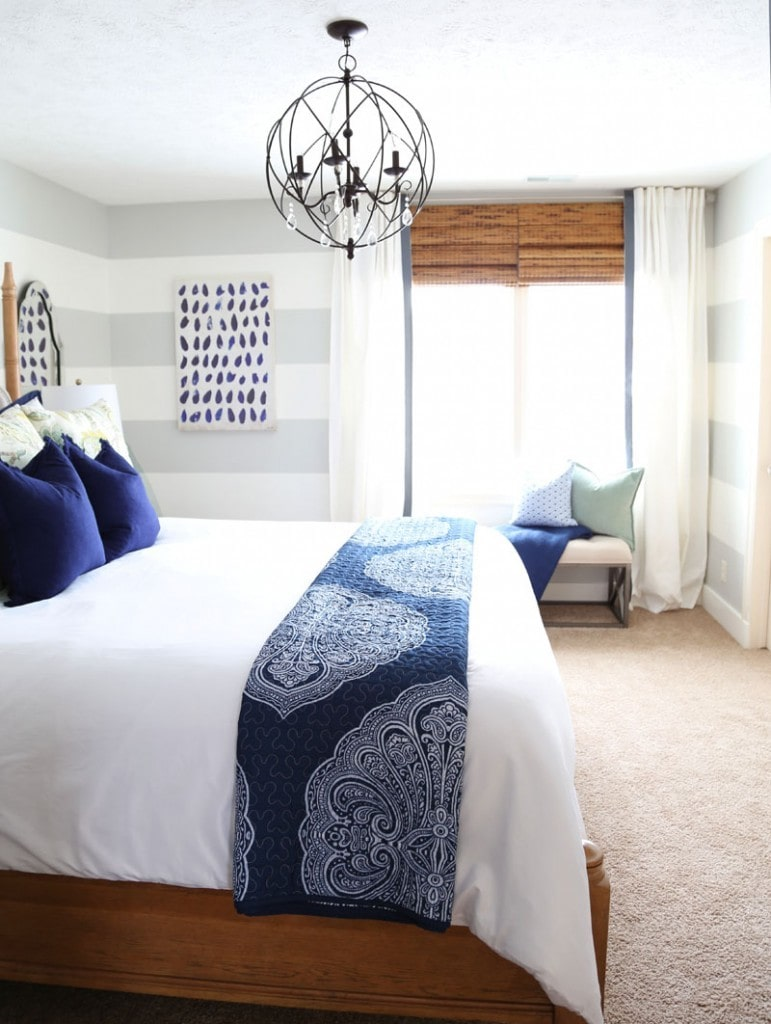 Bamboo shades on the window, blue pillows on the bed, and a round chandelier over the bed.