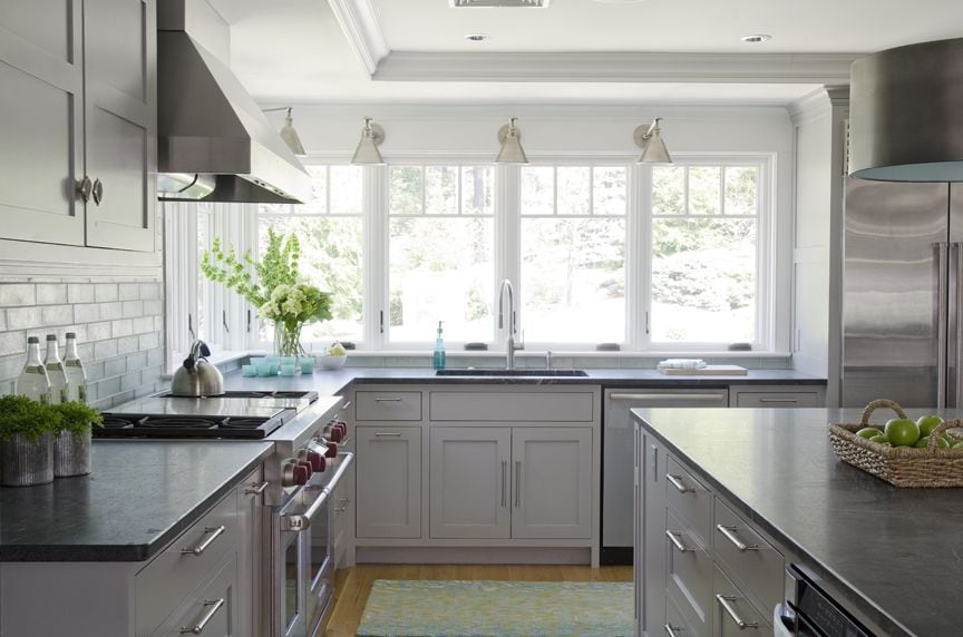 Gray Kitchen with swing arm lights and fruit in a basket on the kitchen island.