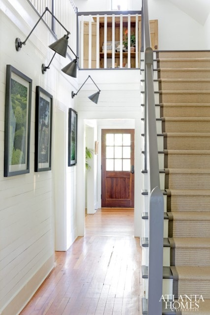 A narrow hallway with steep stairs and swing arm lights in the hallway.