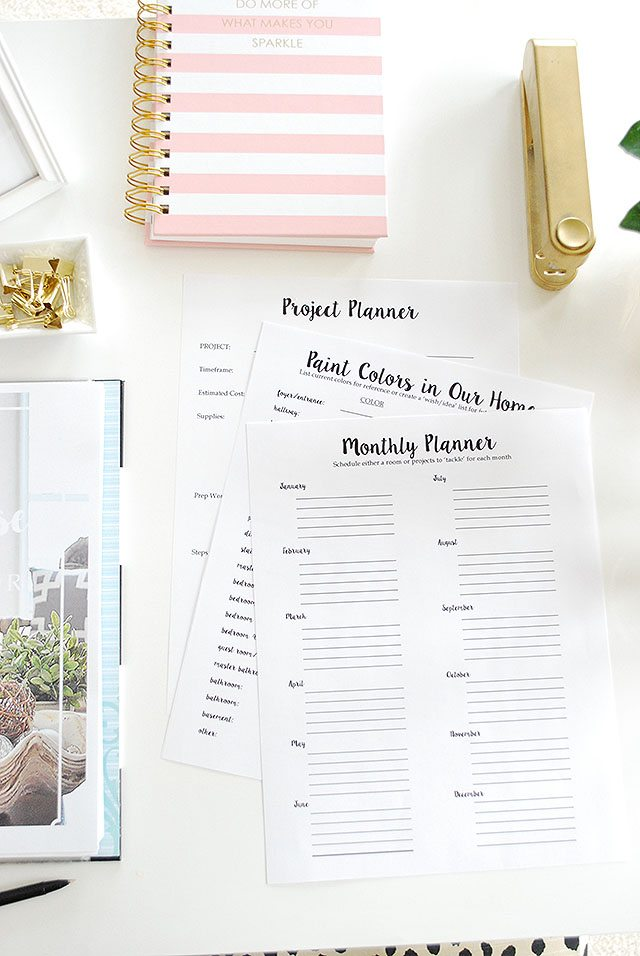 Monthly planners with a pink striped planning book on the desk.