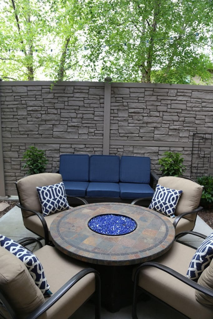 A neutral outdoor courtyard with blue cushions and blue and white pillows.