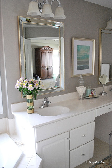 A bathroom with white cabinets,mirrors rimmed with gold and flowers on the white counter.