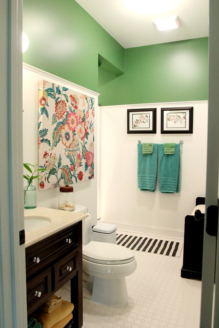 A small bathroom with an wall half green, a floral print on the wall and a dark wood cabinet with a white counter.
