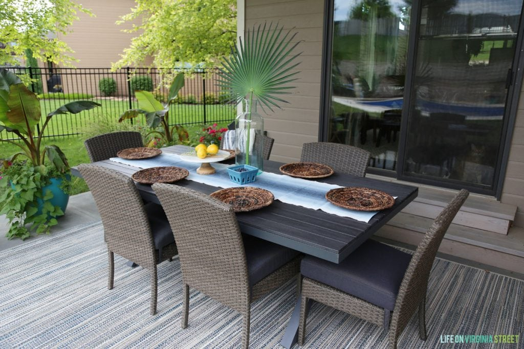 Outdoor table setting before the decor change with lots of brown, table, chairs and rug.