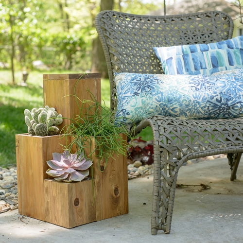 A wicker chair with pillows on it outside.