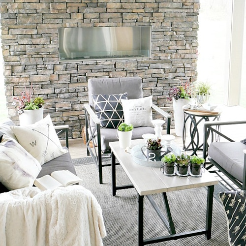 Stone wall with outdoor table and chairs.