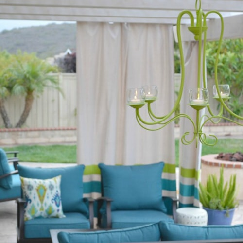Outdoor chandelier with a blue couch.