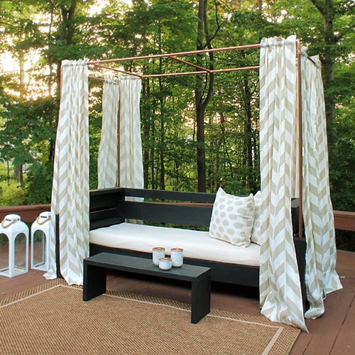 An outdoor daybed with curtains around it.