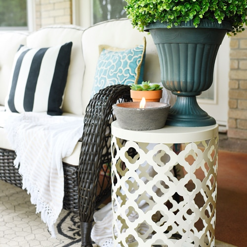 An outdoor chair with white pillows and a side table with candles and plants on it.