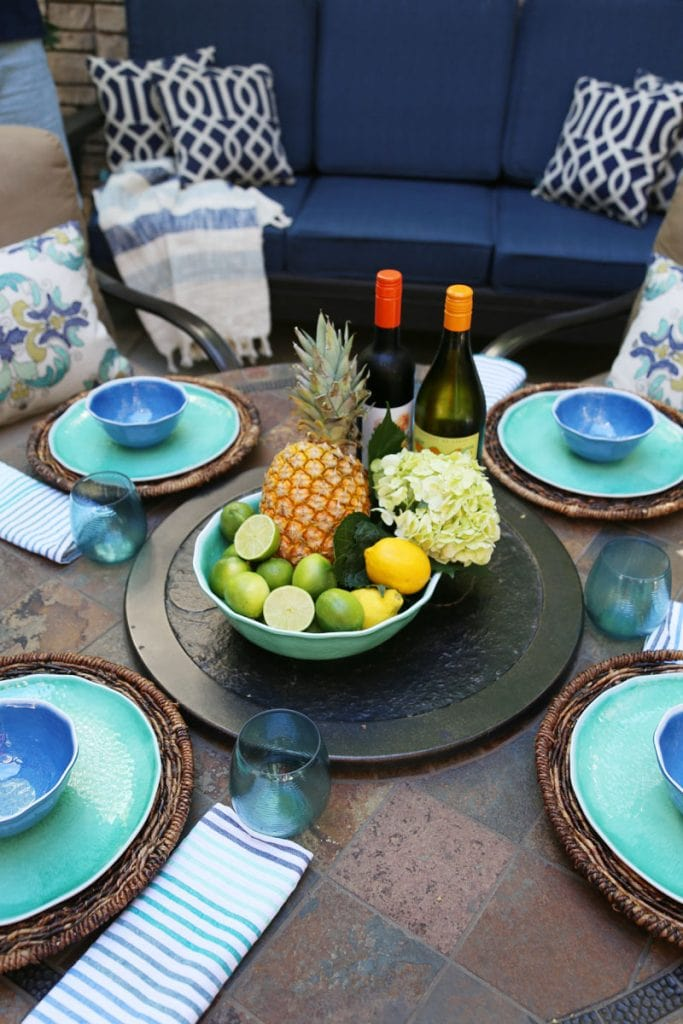Summer Patio with wine, fruit and the table set on the patio.