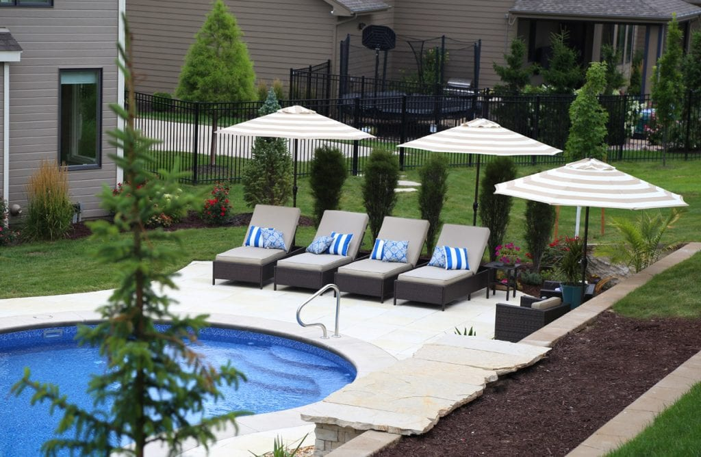 Pool Deck with Lounge Chairs and blue striped pillows on the chairs.