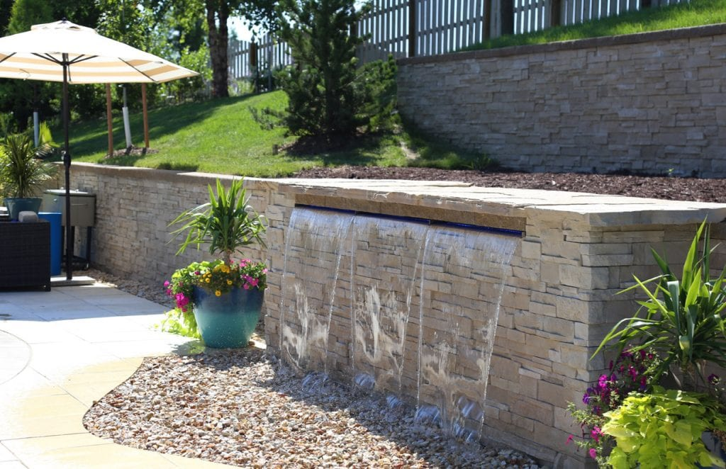 Pool Water Feature with stone and brick at the side of the pool deck.