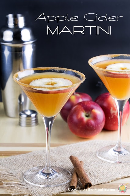 Martini glass with apple cider in it and an apple on top.