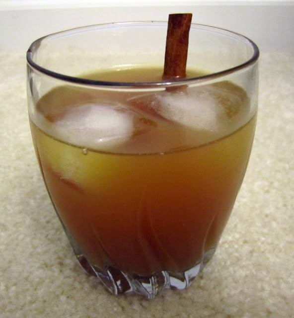 Apple cider vodka in a clear glass with ice and a cinnamon stick.