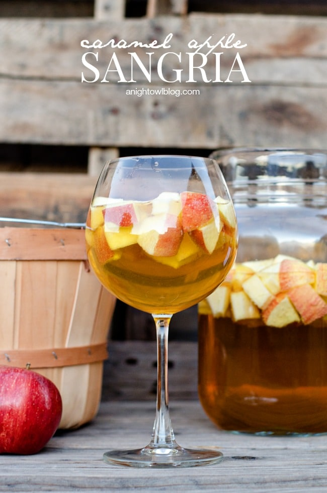 Wine glass with caramel apple sangria inside it, and a red apple beside it.