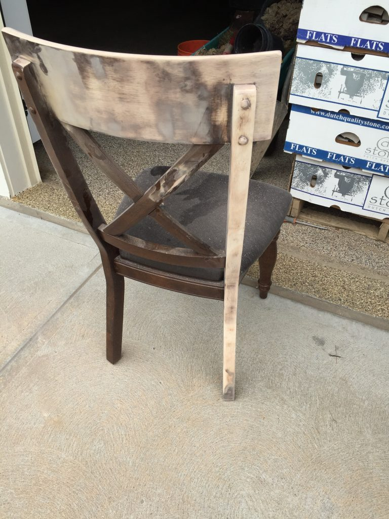 Sanding dark stain off of a dining room chair.