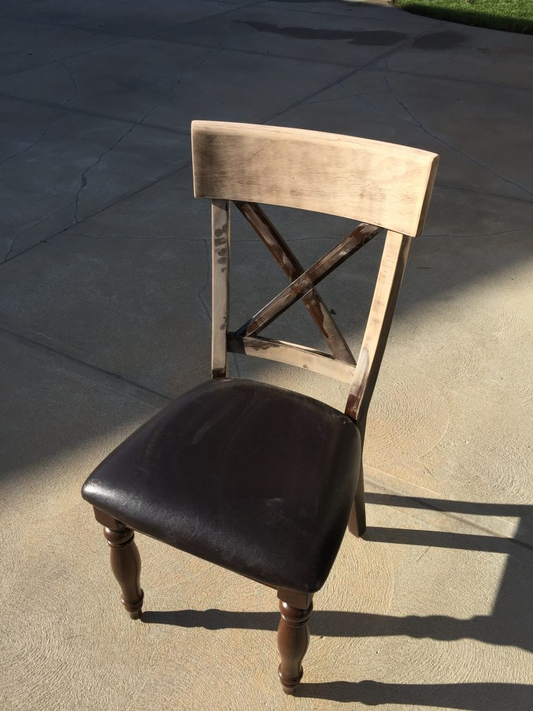 The chair being sanded with a dark leather cushion.