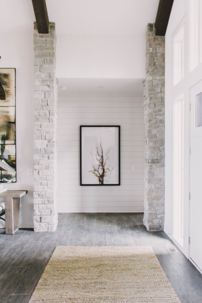 Neutral living entryway with vaulted ceilings, wood beams, white walls and sisal rug. Omaha Street of Dreams. Image via Mandy McGregor Photography.