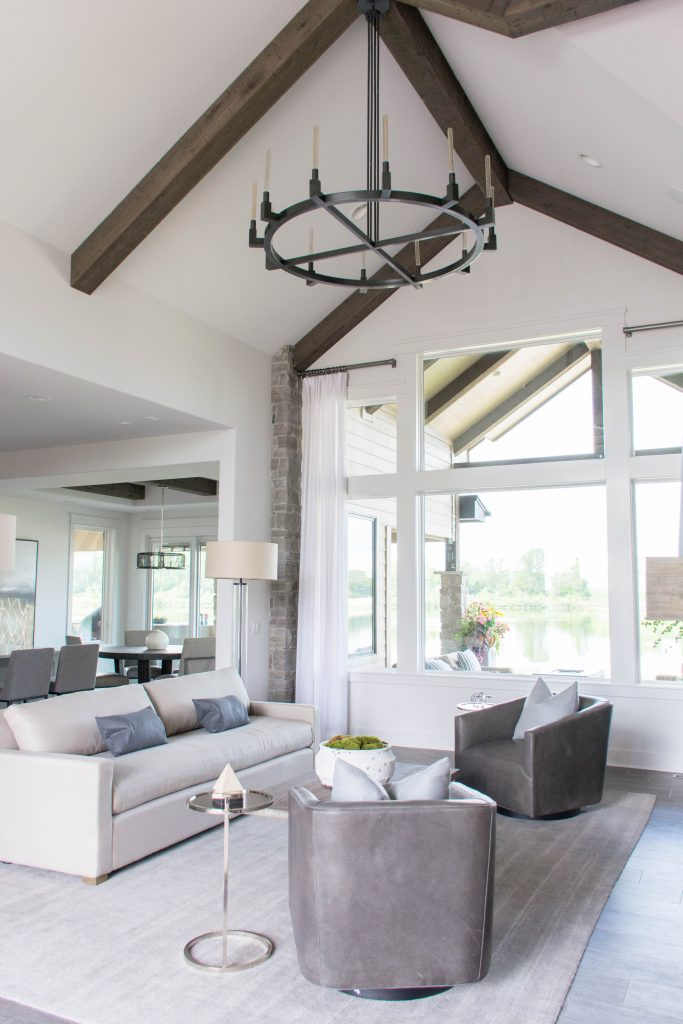Neutral living room with vaulted ceilings, wood beams, white walls and blue and gray accents. Omaha Street of Dreams design by Pearson & Company. Image via Mandy McGregor Photography.