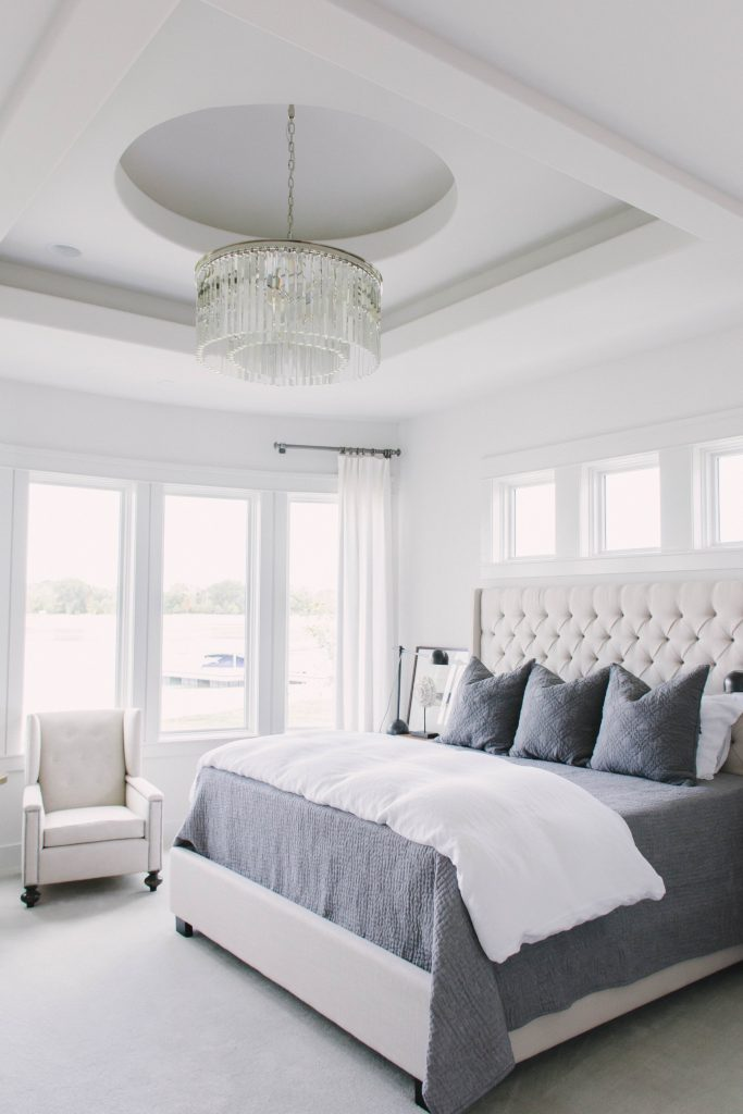 Neutral master bedroom with gray and blue accents and lake views. Omaha Street of Dreams design by Pearson & Company. Image via Mandy McGregor Photography.