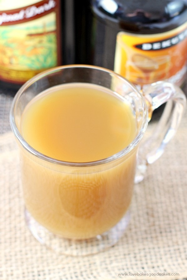 Spiked hot apple cider in a clear mug.