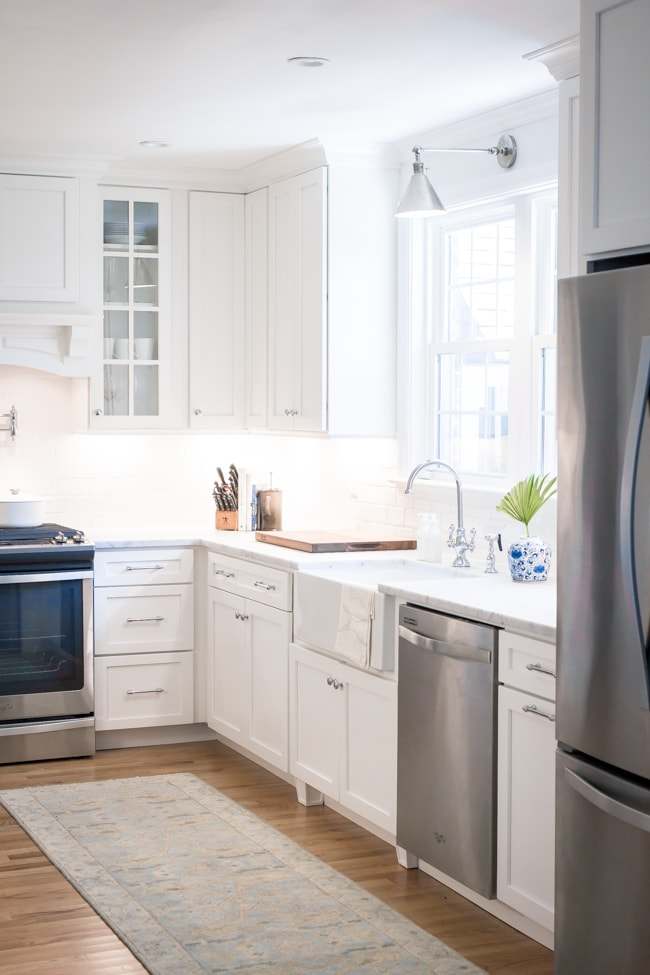 White kitchen with light wood floors and silver accents