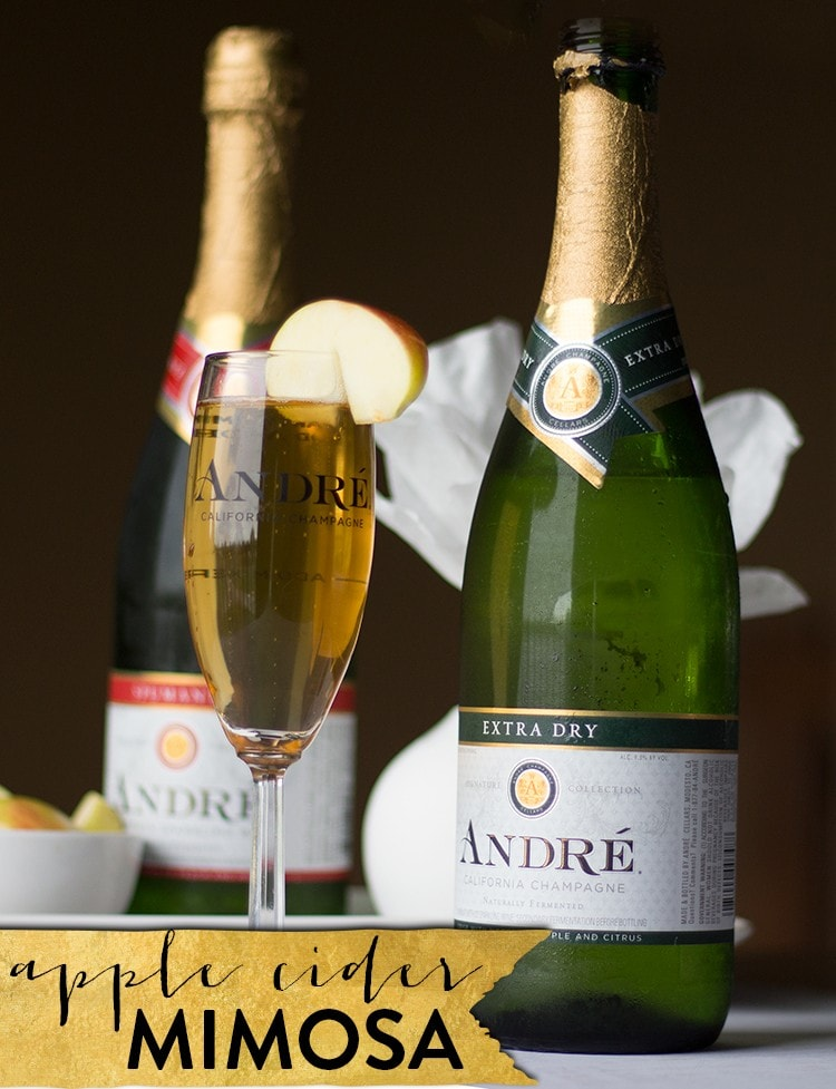 Apple cider mimosa in a champagne glass with champagne bottles behind it.