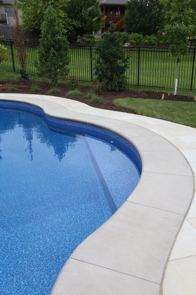 A pool with coping and pavers.