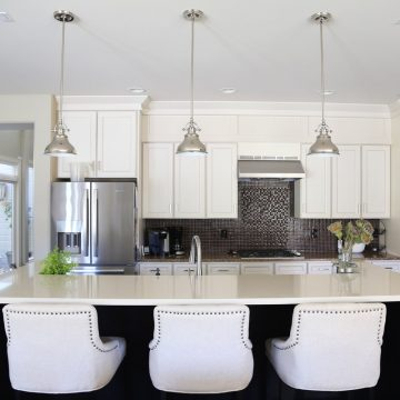 white-kitchen-cabinets-with-black-island-and-linen-barstools-via-life-on-virginia-street