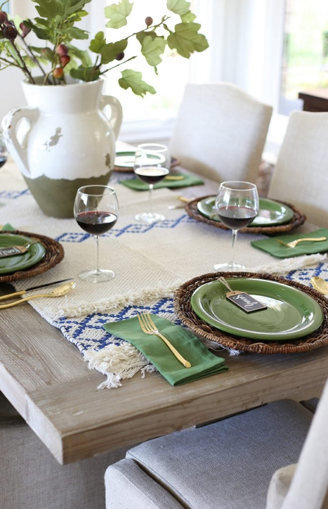 Table set for thanksgiving with green plates, and napkins and white and blue table runner.