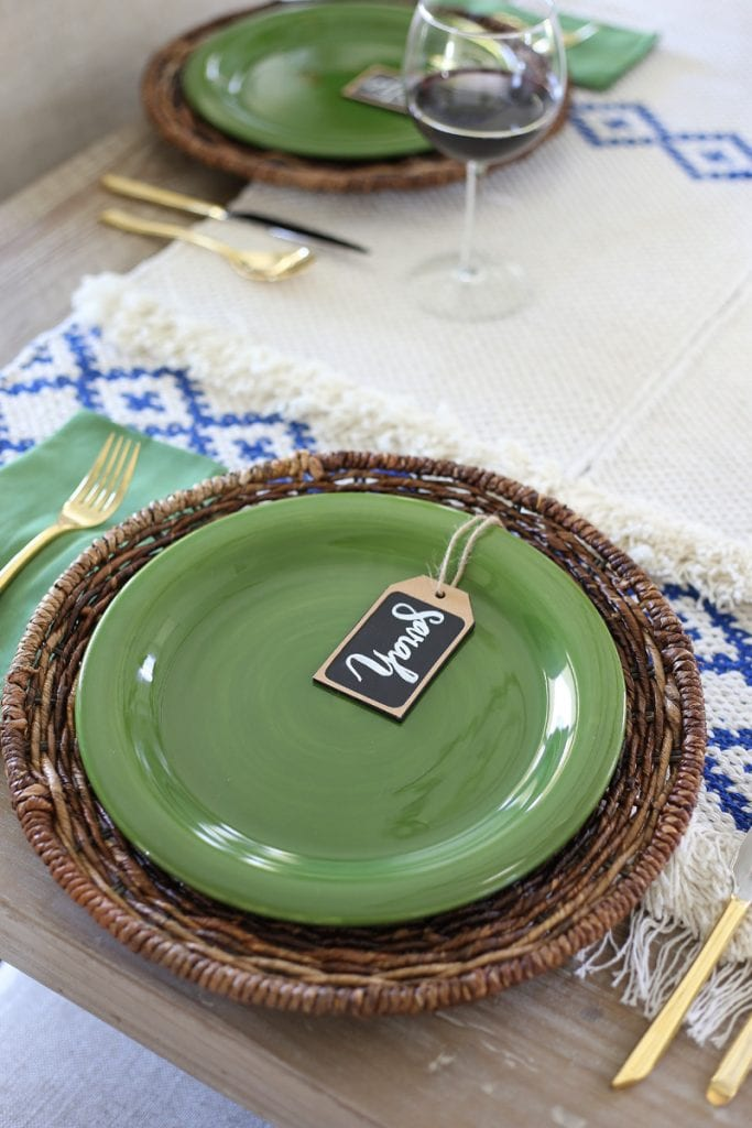 Green plates on a wicker charger with name place tags on plates.