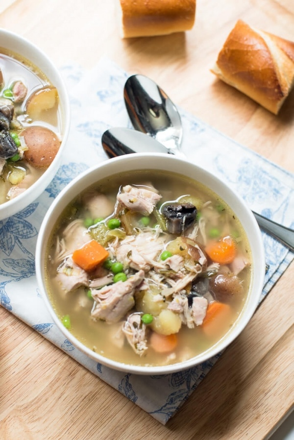 Chicken and vegetable soup on table with bread.