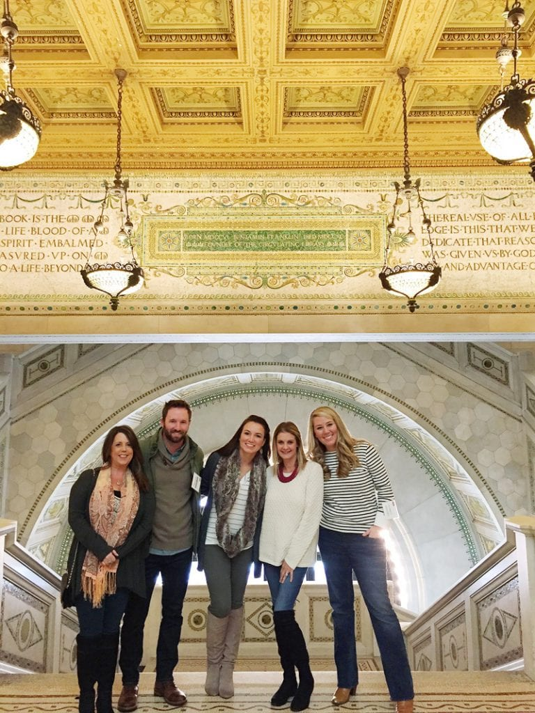 The blogger influencers taking a picture in front of the ornate ceiling, tile and chandeliers.