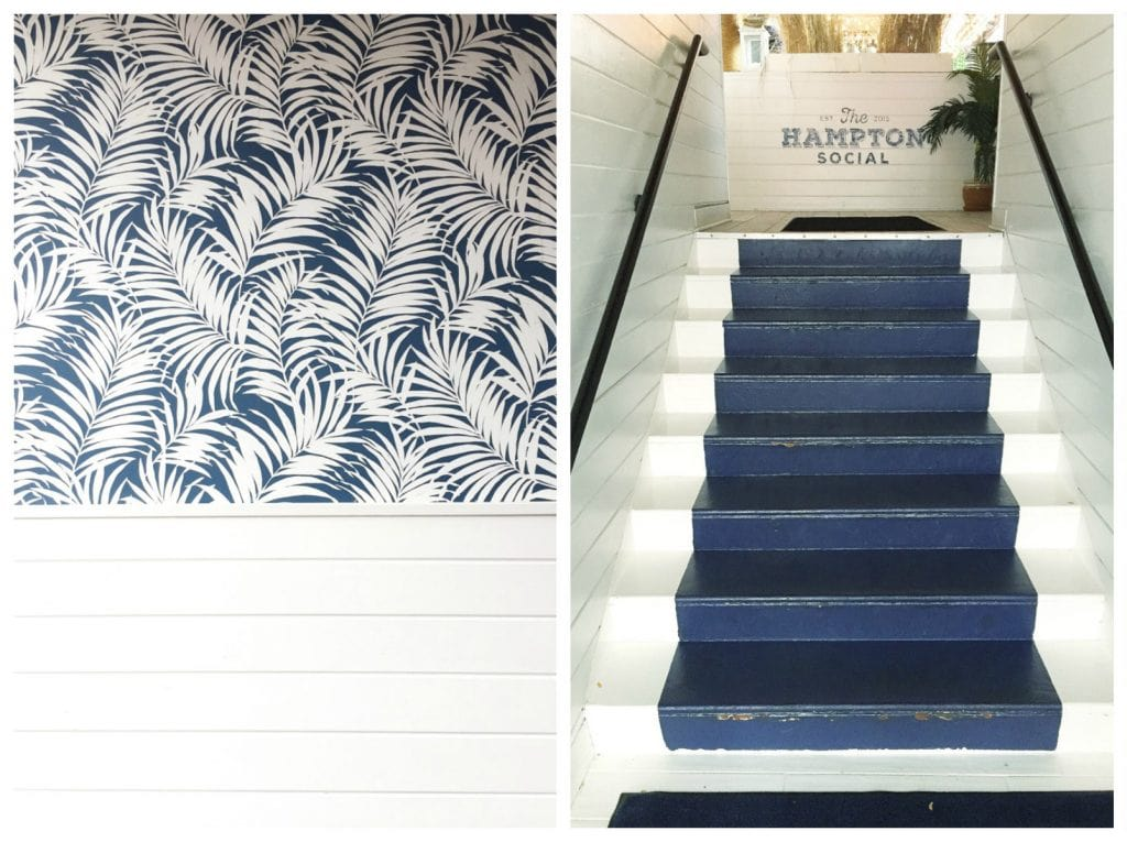 Navy and white wallpaper, and a navy blue painted runner on the stairs.