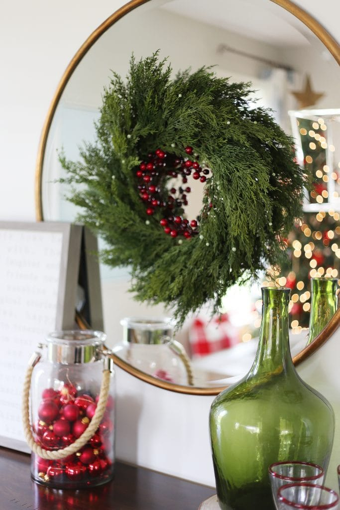 Green Christmas wreath with red berries on a gold mirror in dining room.