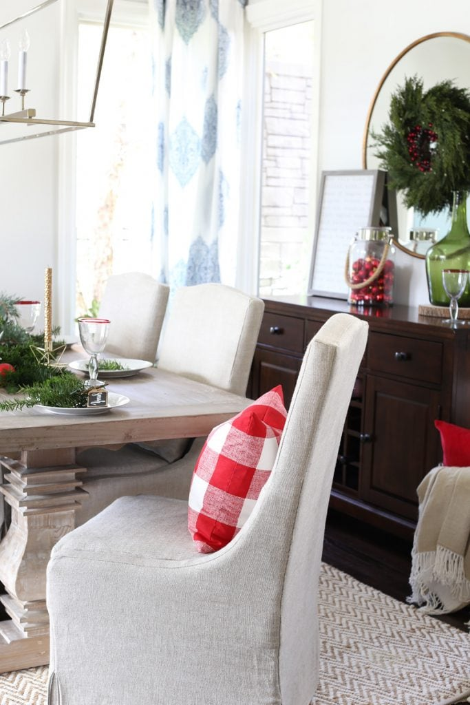 Christmas dining room with Orient Express Collette Dining Chair and a checkered red and white pillow on it.