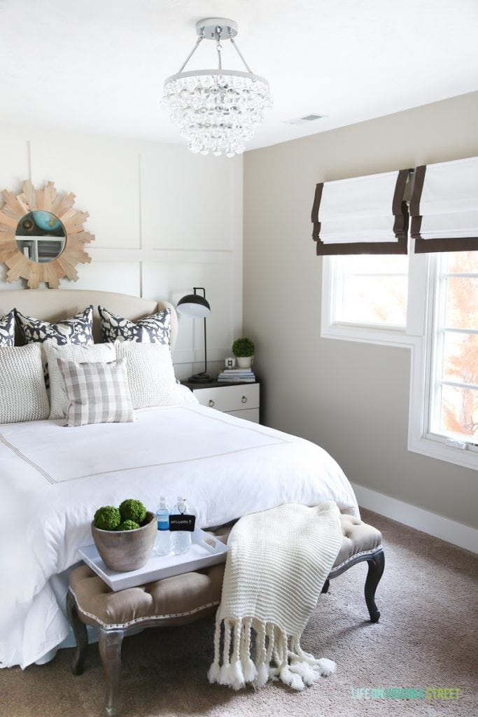 Guest bedroom with neutral bedding and green accents. Great tips on how to prepare your guest bedroom for the holidays!