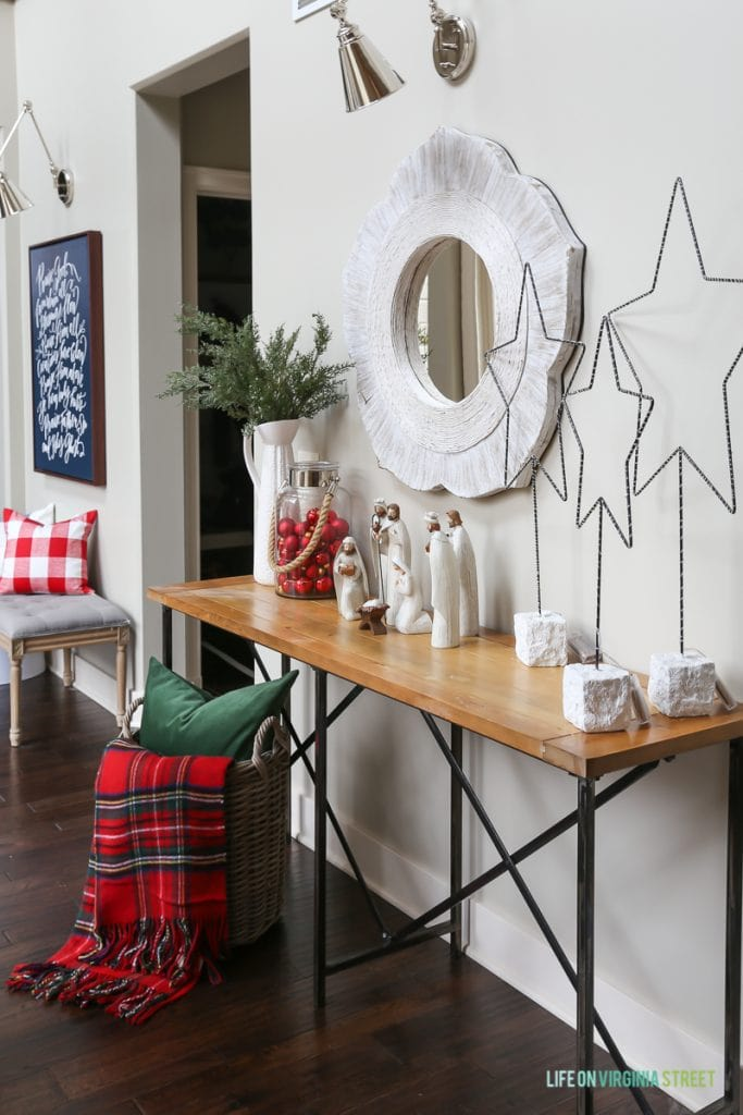Hallway Christmas decor with red plaid, metal stars and nativity scene.