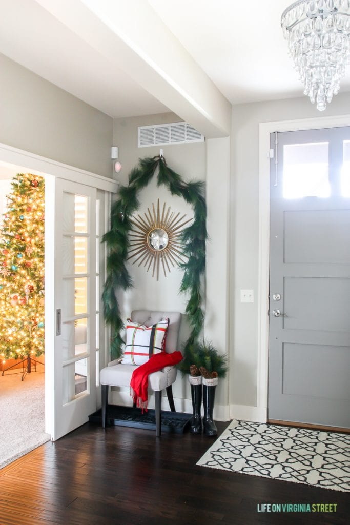 Red and Green Plaid Christmas Entryway with gray door and starburst mirror.
